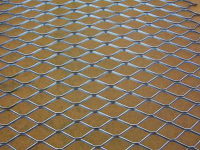 A piece of aluminum decorative expanded metal mesh on the ground.