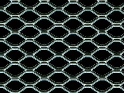 A piece of hexagonal expanded metal car grill on the black background.