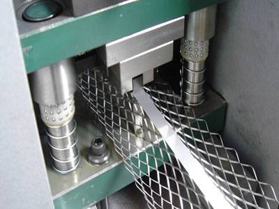 A working machine is producing expanded metal corner bead.