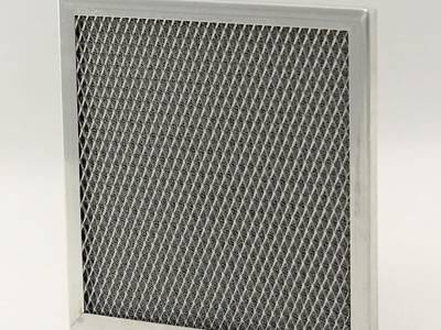 A knitted wire mesh filter panel on the gray background, with expanded metal mesh supporting.