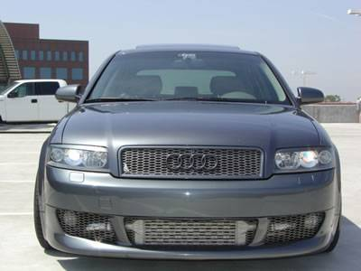 An Audi car parking on the ground with hexagonal hole expanded metal car grill on it.