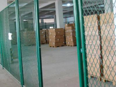 Green expanded metal mesh is surrounding an area with several cartons in it.
