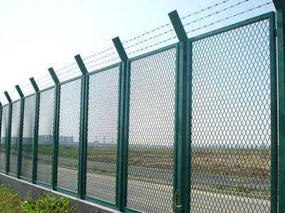 Expanded metal security fences are installed on the road.