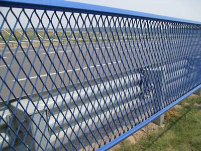 Blue expanded metal security fences are installed on the highway.