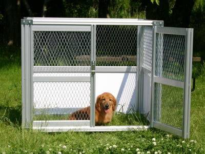A dog is in a cage made of expanded metal security fence with one door opening.