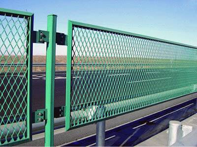 Green expanded metal security fences are installed on the highway.