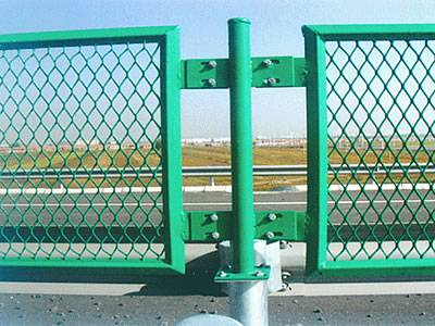 Two green expanded metal security fences are connected by the round post.