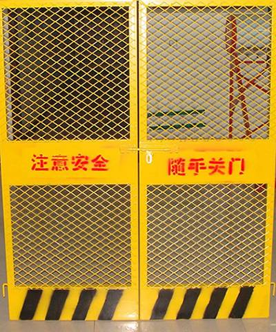 Two elevator gates on the ground with warning signs on it.