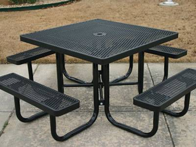 Black expanded metal sheet table and four benches on the ground.