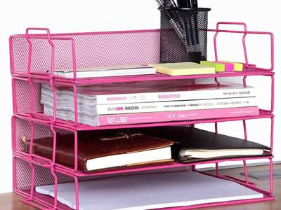 A three-tray pink desk organizer on the desk with books and pens on it.