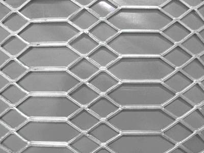 A piece of raised expanded metal sheet with one hexagonal and two diamond hole pattern.