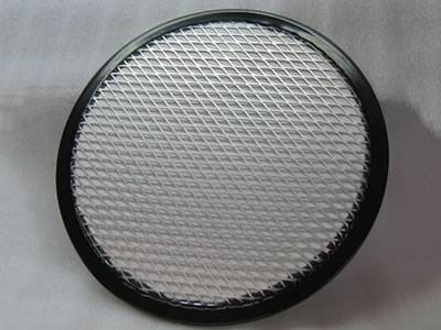 A piece of round stainless steel expanded metal filter element on the gray background.
