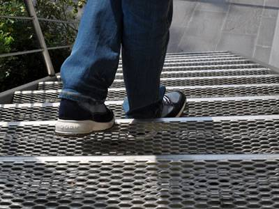 A man is stepping on the stainless steel expanded metal grating.